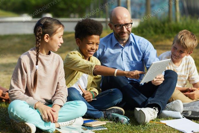 Multiethnische Gruppe von Kindern mit Lehrer im Freien