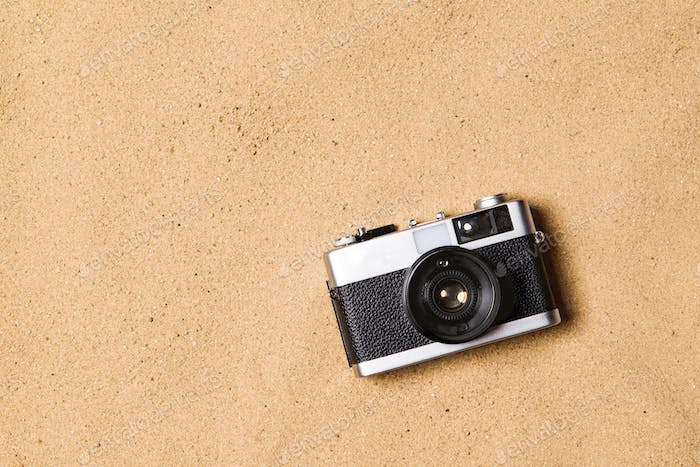 Vintage camera against sandy beach. Studio shot. Copy space.