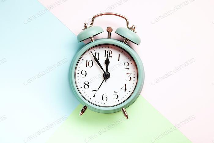 Retro style alarm clock over the pastel background