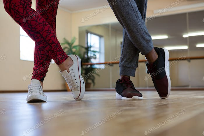 Low section of friends practicing dance on floor