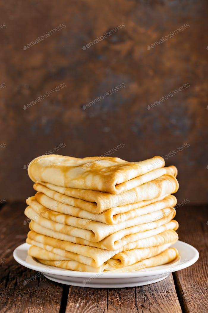 Hausgemachte dünne Crêpes Stapel, gewickelt Pfannkuchen auf Holz rustikalen Tisch