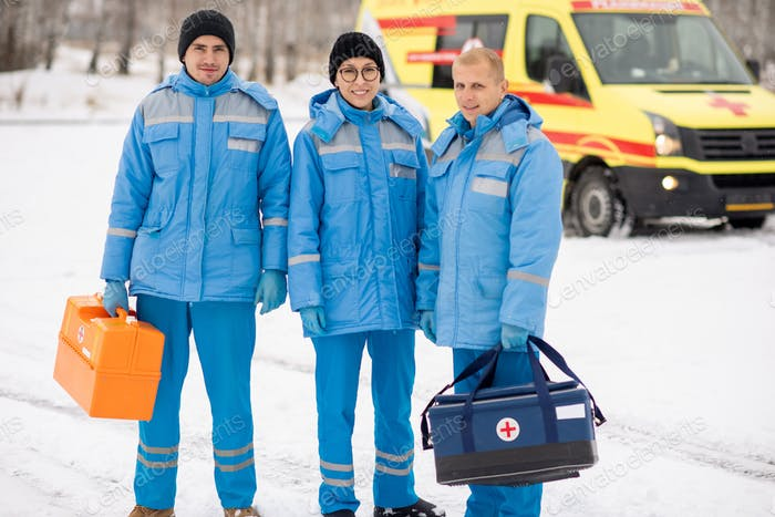 Brigade of young paramedics in blue workwear and gloves holding first aid kits