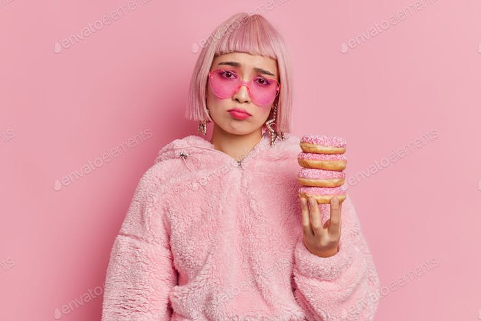 Unhappy frustrated Asian woman with bob hairstyle holds pile of delicious doughnuts feels sad as kee