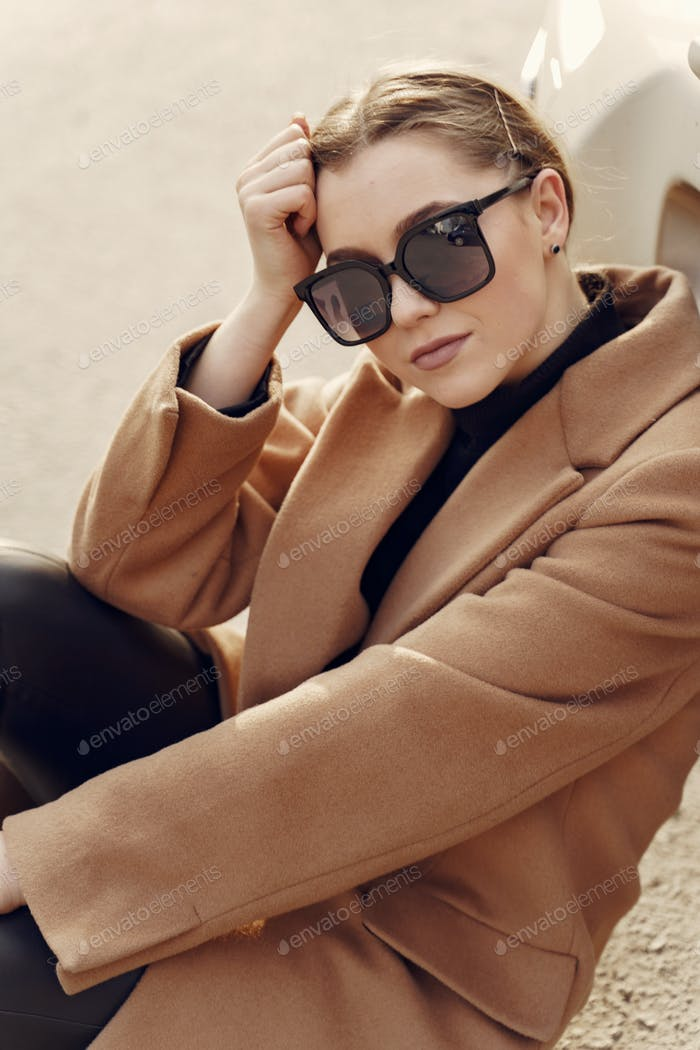 Elegant woman in a brown coat in a spring city