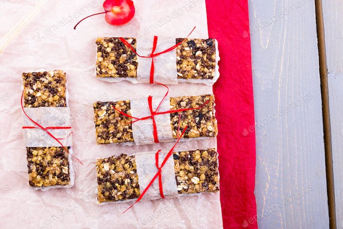 Diet muesli bars on red pepper and wooden background