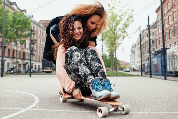 Young woman skating together on a longboard