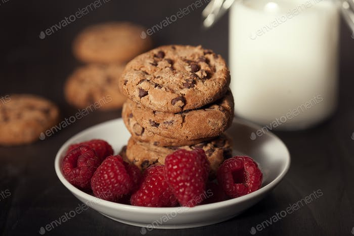 Chocolate chip cookies on white plate dark old wooden table with red raspberry and milk