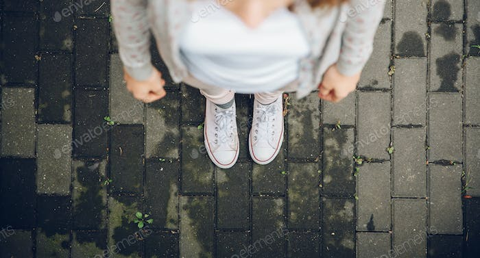Top view of woman feet in white sneakers outdoors