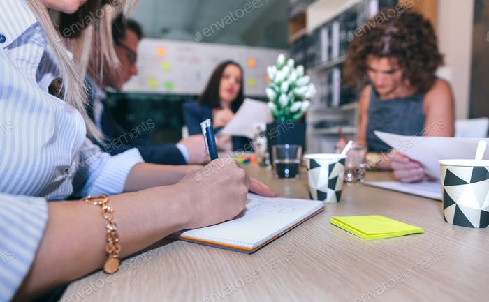 Woman writing notes in a meeting with teamwork