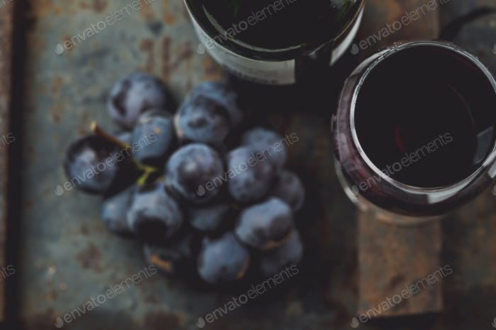 Wine bottle, glass and grape on vintage background.