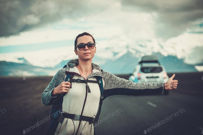 Travel hitchhiker woman walking on a road