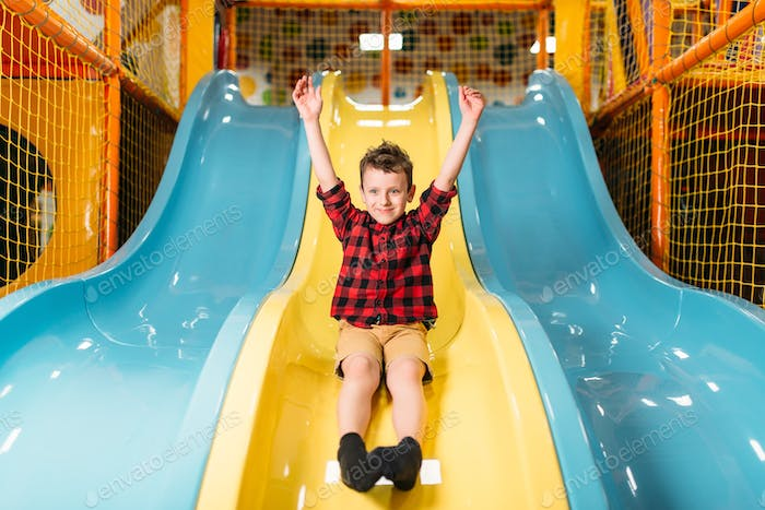 Boy riding from childrens slides on playground