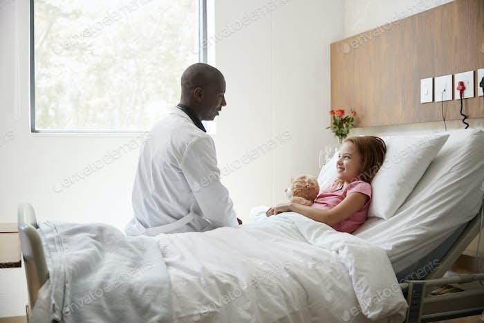 Male Doctor Visiting Girl Lying In Hospital Bed Hugging Teddy Bear