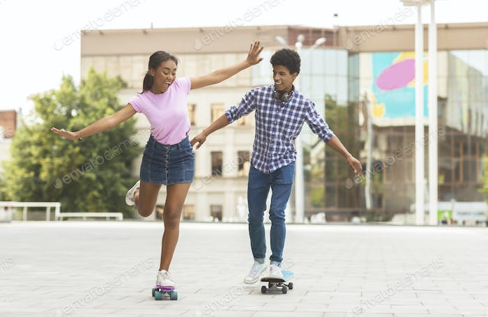 Happy teenage couple riding modern cruiser skateboards on city street