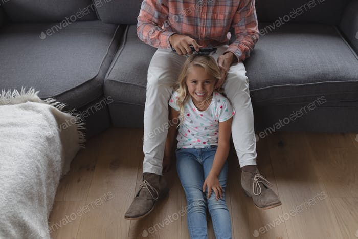 Front view of Caucasian father combing her daughter hair in living room at home