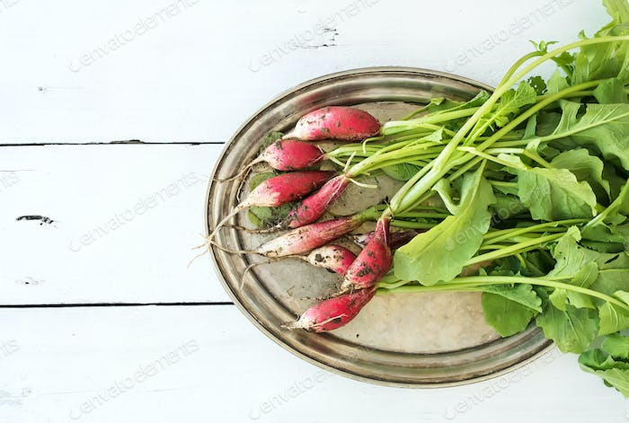 Bunch of fresh dirty garden radishes on vintage metal tray
