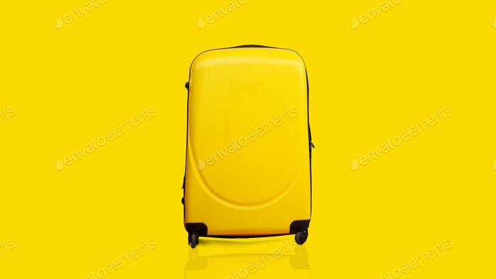 Yellow suitcase over yellow background, panorama with copy space
