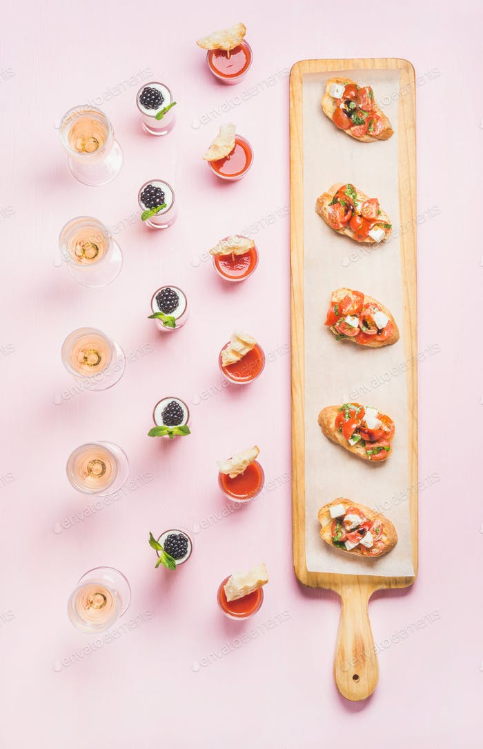 Various snacks, brushetta sandwiches, gazpacho shots, desserts over pink background