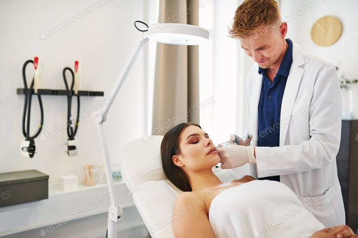 Young woman receiving botox injections at a beauty clinic