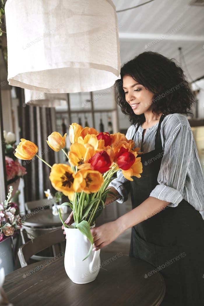 Довольно флорист в фартуке создавая букет тюльпанов