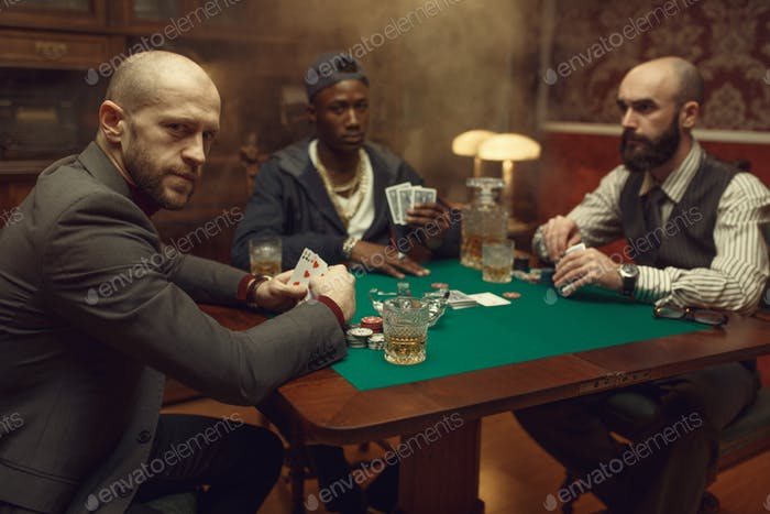 Poker players with cards playing in casino