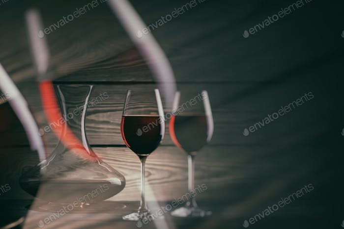 Two glasses and decanter of red wine on a dark background