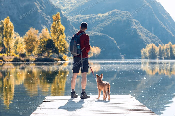 Hiker young man traveler with backpack with his dog looking the landscape in the lake.