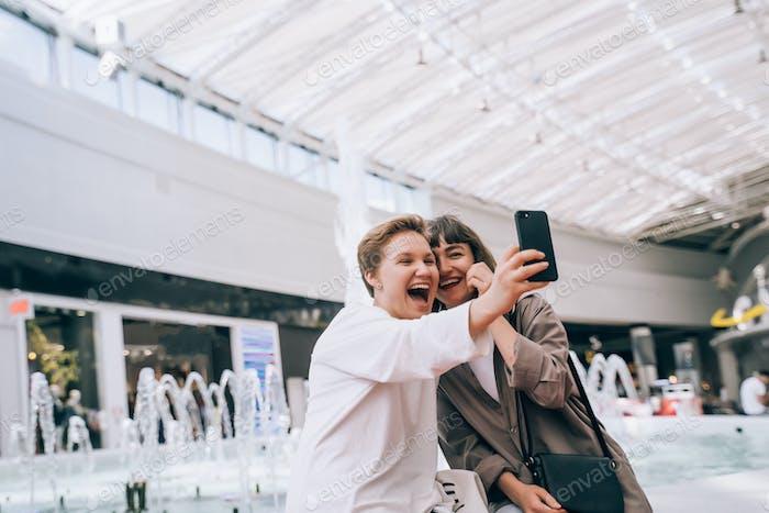 Zwei Mädchen nehmen ein Selfie in der Mall, einen Brunnen im Hintergrund