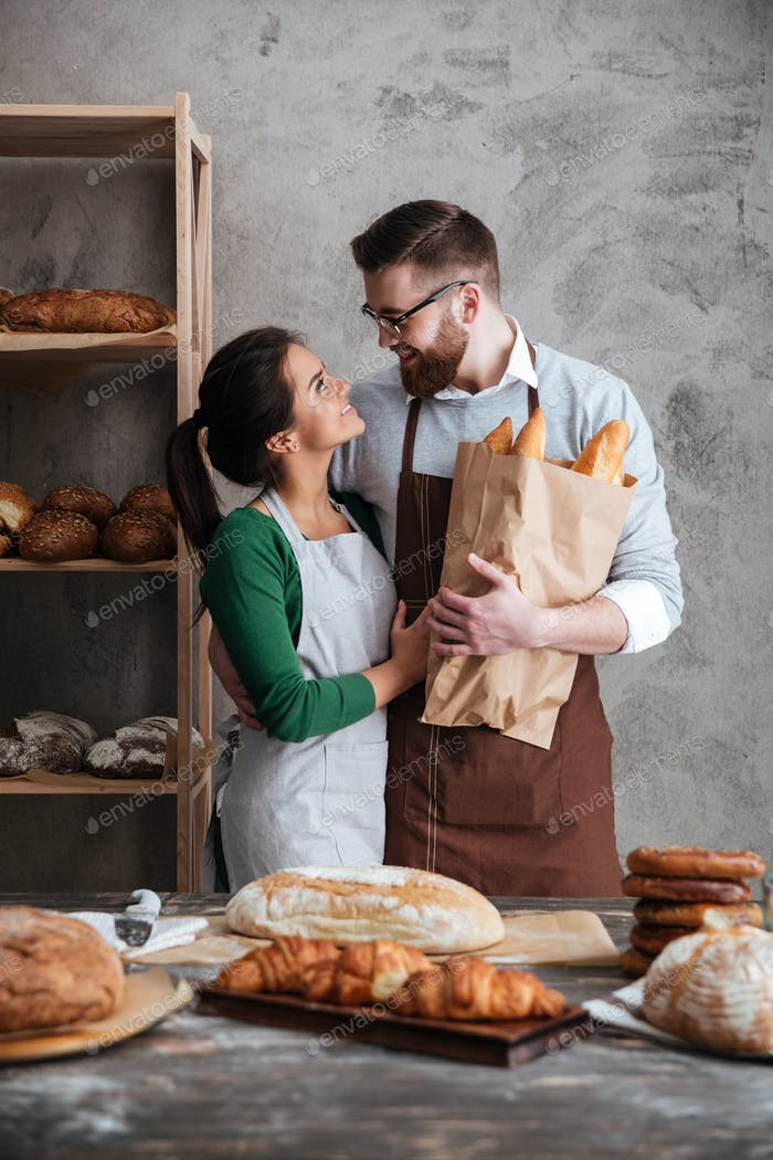 Vertical image of happy bakers in bakery