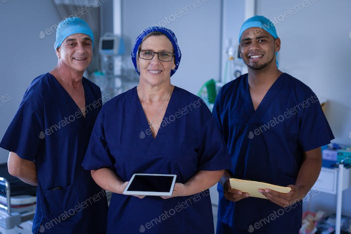 Surgeons smiling to the camera while standing with a digital tablet and folder in hospital clinic