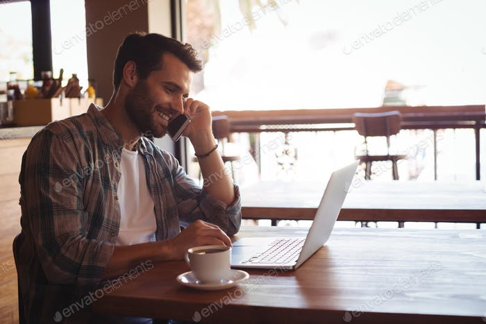 Man talking on mobile phone while using laptop