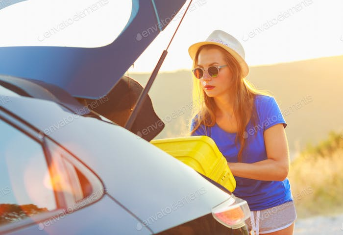Woman loading luggage into the back of car parked alongside the