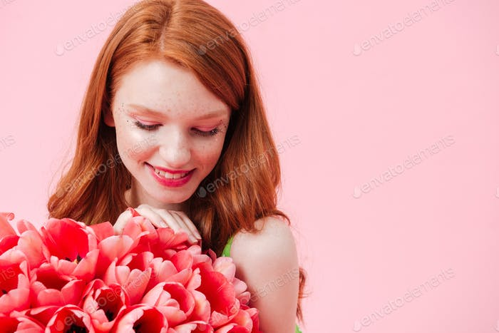 Close up portrait smiling woman holding bouquet of flowers