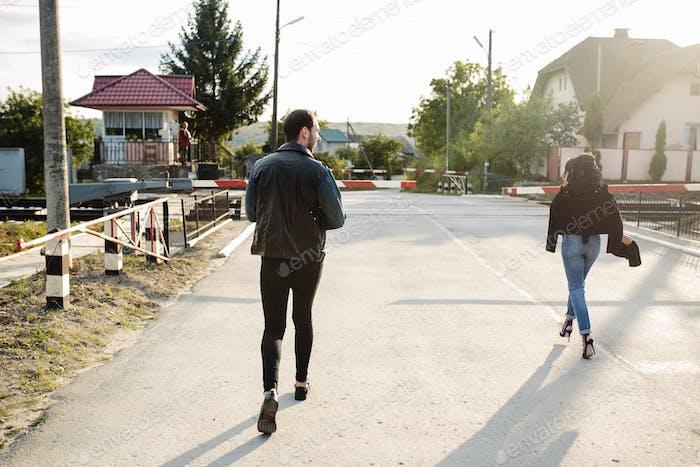 Mann und Frau laufen zum Bahnübergang