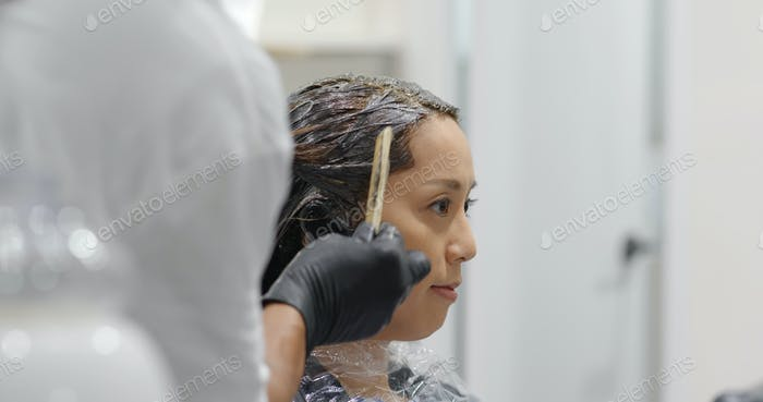 Woman undergo hair color dye in beauty salon