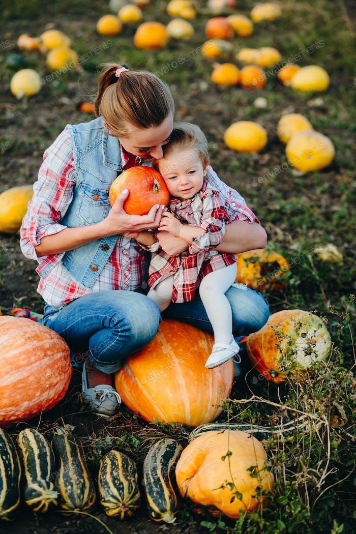 Mutter und Tochter sitzen auf Kürbisse