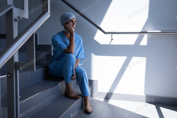 Thoughtful female surgeon sitting on stairs in hospital