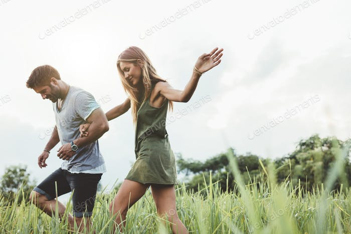 Young couple walking through meadow