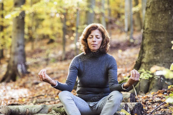 Senior woman meditating in an autumn forest.