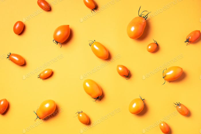 Yellow tomatoes pattern on bright background. Flat lay, top view. Summer minimal concept. Vegan and