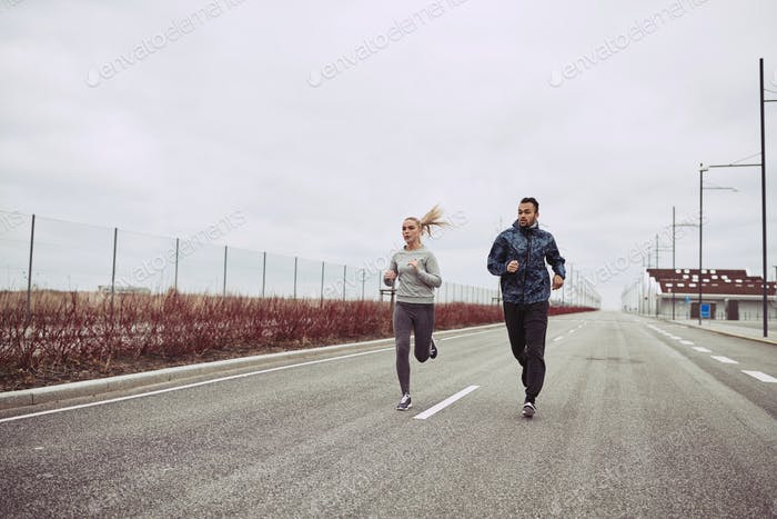 Young couple in sportswear running together along a country road