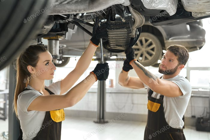 Woman and man fixing undercarriage of car in autoservice
