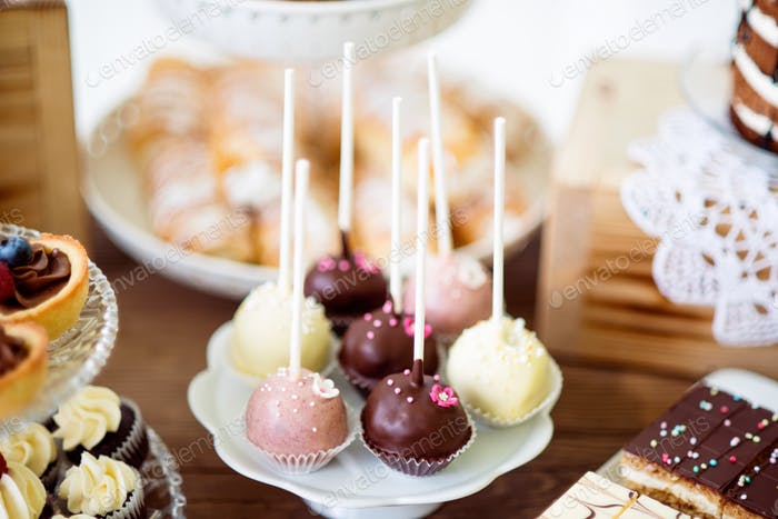 Cake pops on cakestand, tarts and cupcakes. Candy bar.