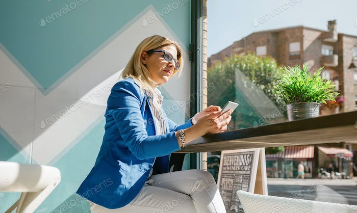 Working woman thinking and holding phone