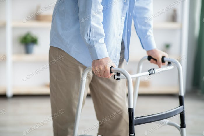 Cropped view of elderly man walking with frame at home, closeup. Disabled older person in need of