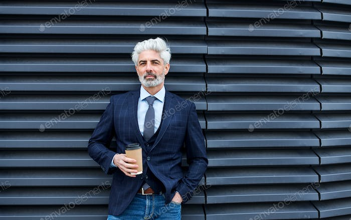 A mature businessman standing outdoors, holding coffee. Copy space