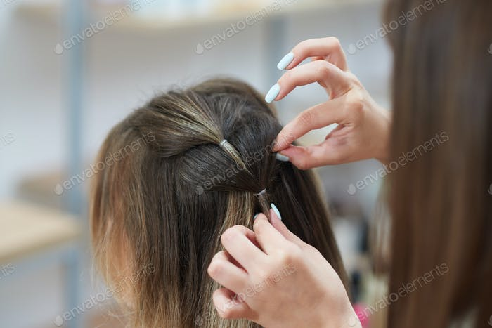 Selective focus of hands of hairdresser braiding spikelet to client in beauty salon