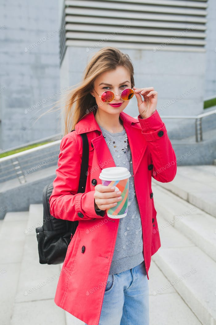 young hipster woman in pink coat, jeans in street