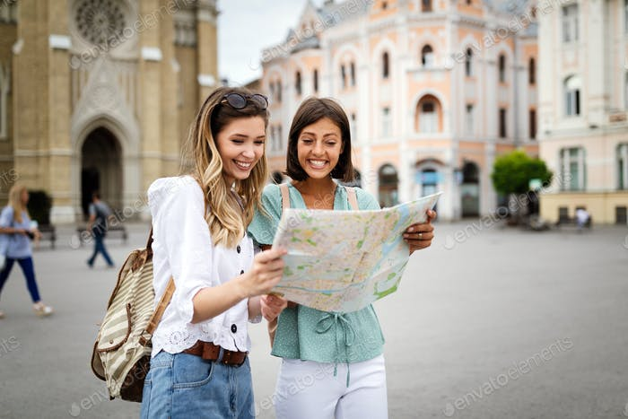 Happy travel together of two beautiful women in city centre