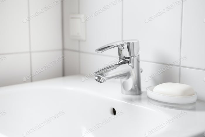 White ceramic sink with faucet and soap